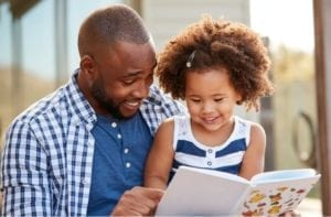 A father reading aloud with his daughter
